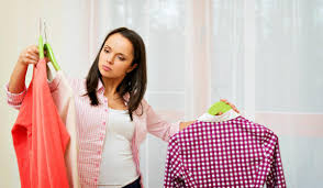 young brunette woman choosing clothes in home interior spring cleaning tips for your bedroom
