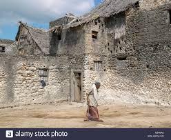Kenya, Pate Island, Pate Village. An elderly man strides past a ...