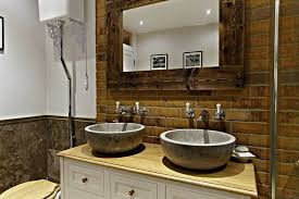 This bathroom looks stunning with stone tiles and exposed brick walls