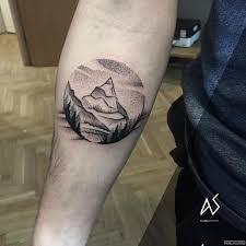 горы с деревьями в круге тату на предплечье у парня добавлено