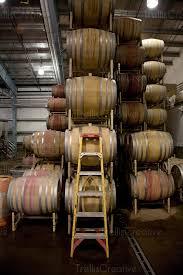 oak barrels stacked top. A Ladder Leans Against Several Stacked Oak Wine Barrels Top