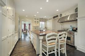 White Kitchen Features Extensive Shelving, Dual Brushed Aluminum Ovens, And  Large Central Island With