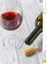 Light Burgundy Wine Red Wine In A Glass And A Bottle On A Light Wooden Table