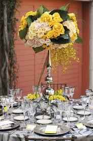 Tic Tock Florals, Contemporary Elevated floral centerpiece of yellow roses,  yellow oncidium orchids and yellow cymbidium orchids