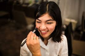 a stylist works on the makeup for anese model rina ushi
