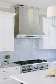 steel french kitchen hood with gray marble arabesque tiles