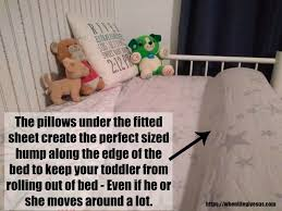 image of a bed with two bolster pillows secured under the fitted sheet to create a