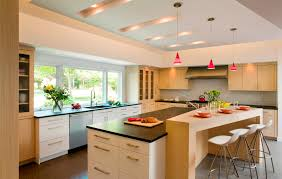 lovely red funnel glass pendant lights over white kitchen island drawers and black top as well as wide glass windowed as well as white cabinetry sets in