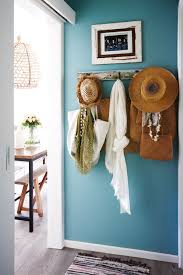 entryway with ppg sea blue walls and weathered hooks with hats and scarves