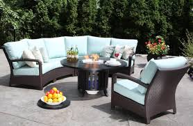 patio chair sale discount outdoor furniture blue sectional sofa and white cushions with fire pit table on the center and some bottle glass plate lemon flower