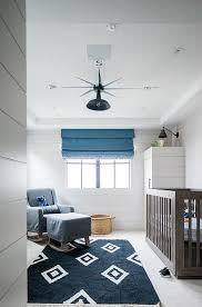 brown nursery crib with navy blue rug