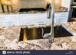 New Modern Faucet And Kitchen Sink Closeup With Island And Granite