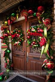 Christmas garland and matching wreaths make this doorway fun and inviting.  www.showmedecorating.