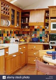 Multi coloured wall tiles in kitchen dining room with fitted pine cupboards  and white ceramic sink