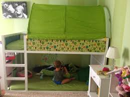 bedroom white wooden bunk bed with stars and green tent and bed sheet placed on