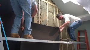 a crew from new england soundproofing applies a sound deadening mass loaded