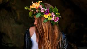 woman standing on dark area with flower crown how to make a flower crown
