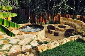 Small Round Rattan Table Wooden Hot Tubs Around Vertical Wooden Fence And Curved Rock Bench