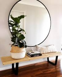 Large round mirror above a wood bench--- for the modern(ish)
