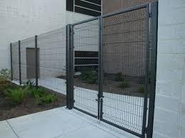 black welded wire fence. Black Welded Wire Security Fence Is Installed Between Two Buildings.
