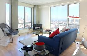 modern small apartment decorating ideas highlighting navy blue fabric loveseat sofa with track arm and rectangle glass coffee table using dari iron frame on
