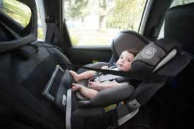 side view of young child strapped into child car seat