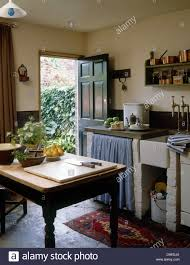 Wooden Table In Center Rustic Country Cottage Kitchen With Curtains