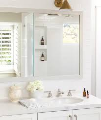 brass bathroom light. white master bathroom features a washstand topped with quartz under framed mirror lining subway tiled wall illuminated by an aged brass light