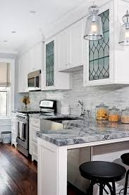 glass building kitchen cabinets. amazing kitchen features white shaker cabinets paired with quartzite countertops and a linear marble backsplash. glass building