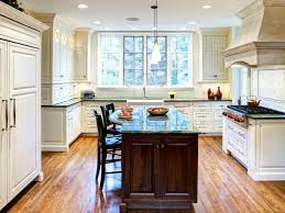 white kitchen with green marble countertops and walnut island