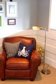 love the white planks 3 horizontal planks modern looking chair rail also love the wall color and that great club chair