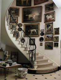 gorgeous gallery wall sweeping up the staircase antique dog paintings