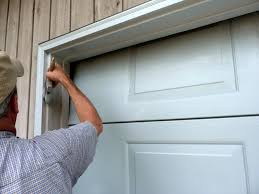 a man in a short sleeved collared shirt and tan baseball cap reaches up to when painting your garage door