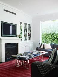 relaxed living room ambiance with grey sofa red rug fireplace and led tv beside book storage image