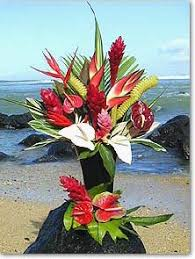 a select holiday arrangment of hawaiian tropical flowers and anthuriums each flower is individually gift wrapped in a flower sleeve and green red tissue
