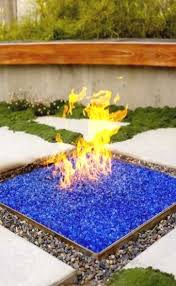 propane outdoor fireplace glass fire pit with blue glass surrounded by river rock
