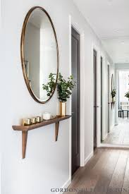 Like the shallow shelf. The Maple Building  Gordon Duff & Linton. View of  hallway with bespoke shelf and bronze trimmed round mirror.