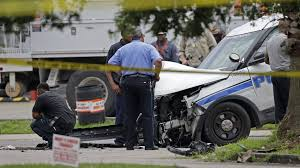 investigators look over a new orleans police department vehicle in which one officer was shot and