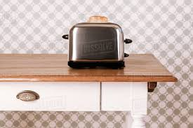 Old Kitchen Table With Toaster And Slice Of Bread In Front Of