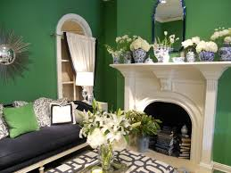 Classic white fireplace offset by kelly green walls, competing patterns,  and a collection of
