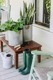 Plants and gardening tools at various heights decorate a front porch