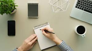 office table ideas. Man Writing Ideas On Daily Notebook Grey Office Table Background. Top View. Shot
