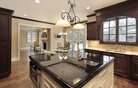 kitchen with wood cabinets and white island with black granite countertop