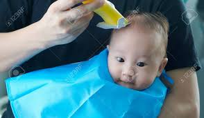 幼児子供用電動バリカンとの彼の最初ヘアカットを得ること の写真素材
