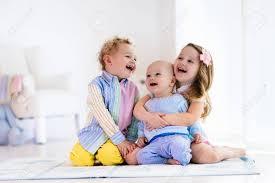 Gruppe Von Drei Kindern In Einem Weißen Schlafzimmer Spielen Kinder