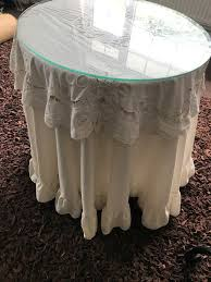 occasional round table with glass top and cream tablecloth immaculate condition