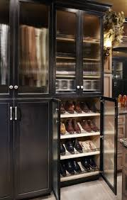 walk in closet features stacked black cabinets accented with glass doors filled with rows and rows of slanted shoe shelves