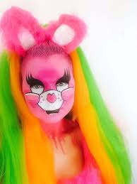 drag queen clubkid care bear pink makeup with pink cartoon face pink fluffy ears headpiece pink orange and green hair pink drips glitter laceylou