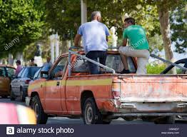Two men stood in the back of pickup truck whilst moving through ...