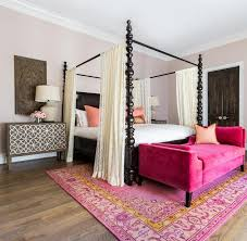 hot pink settee at end of black canopy bed